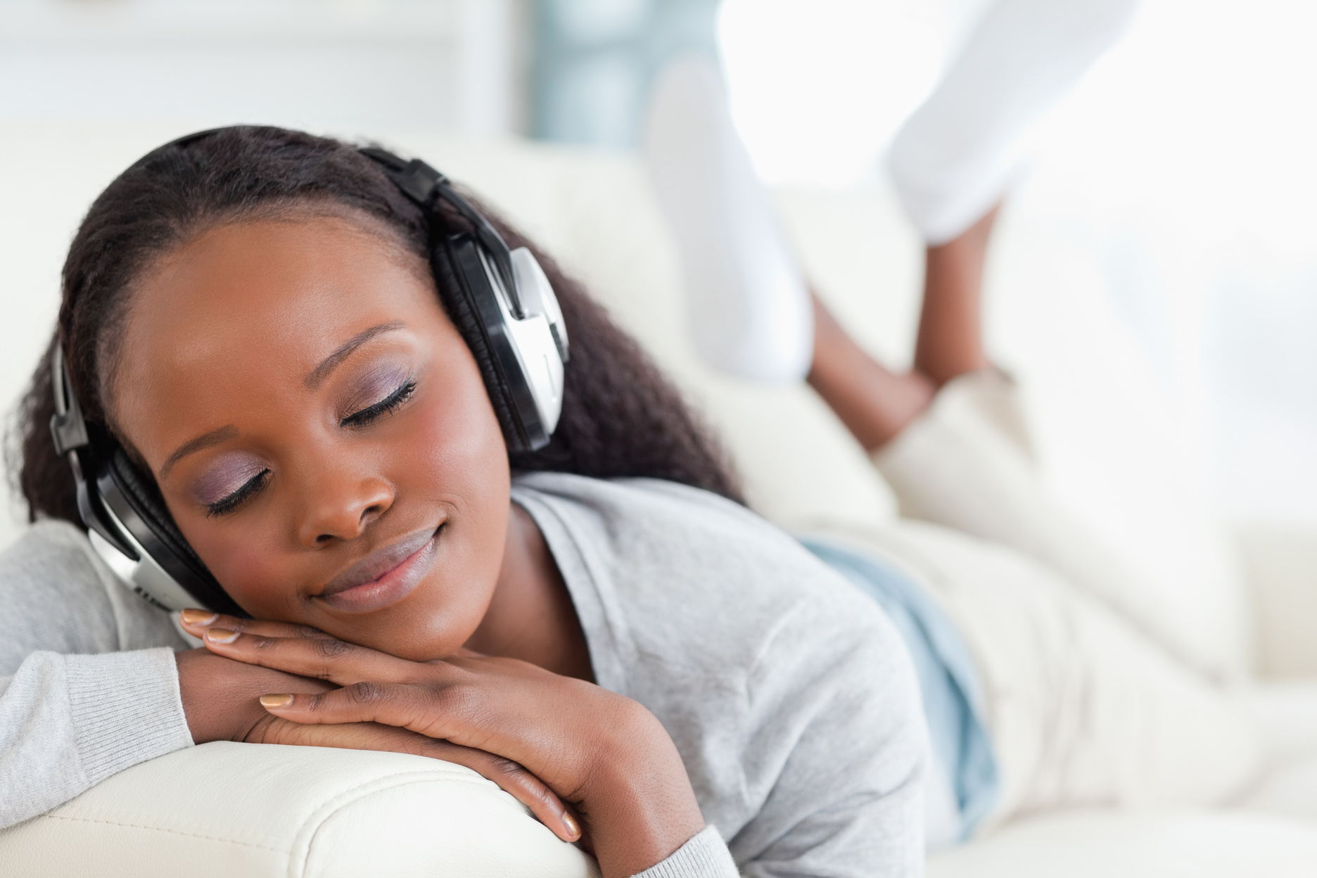 Close up of woman enjoying music on sofa